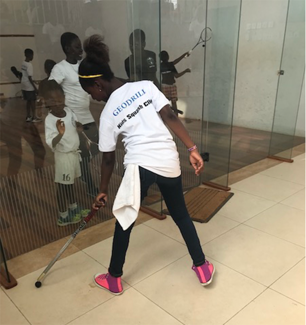 A squash novice trying her hands on the racquet and ball.